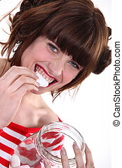 A woman eating marshmallows.