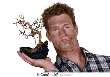 funny picture of man holding bonsai after explosion