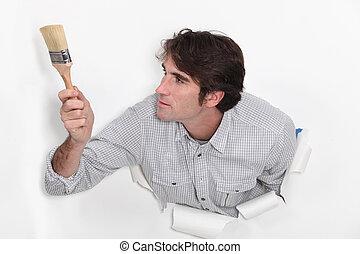 Man with paint brush crashing through poster