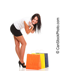 Full length of happy young lady shopping bags against...
