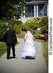 Newlyweds walking up a path
