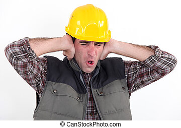 A construction worker covering his ears