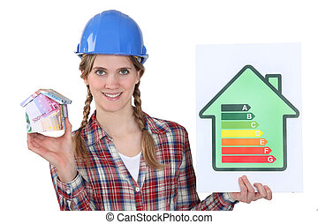female heating engineer holding money box in shape of house