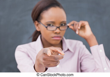 Focus on a strict black teacher pointing finger in a...