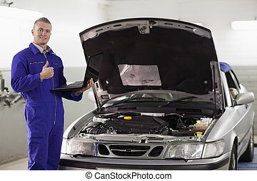 Mechanic holding a computer with thumb up in a garage