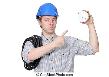 An electrician with a fire detector