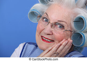 Elderly lady using hair rollers