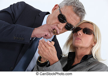 mature gentleman smoking cigar with blonde spouse showing off