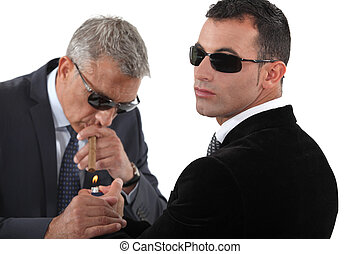 businessmen wearing sunglasses and smoking a cigar