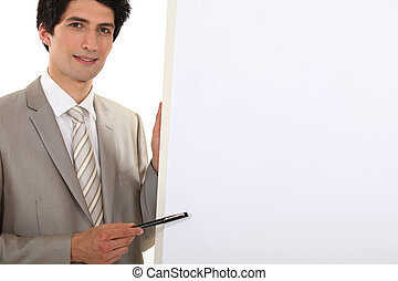Businessman pointing to a blank flip chart