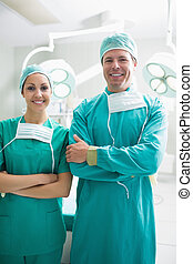 Surgeons looking at camera while smiling in an operating...