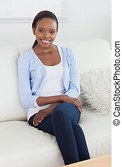 Black woman sitting on a sofa in a living room
