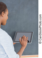Woman using a tablet computer next to a blackboard in a...