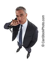 A mature businessman smoking a cigare.