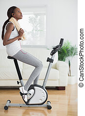 Black woman on an exercise bike holding a towel