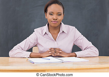 Front view of a black teacher looking at camera in a...