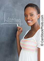 Black woman showing the blackboard in a classroom