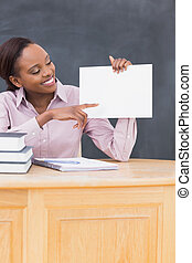 Black teacher holding a blank paper at desk in a classroom