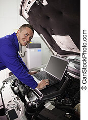 Smiling mechanic working on a computer