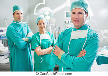 Surgical team smiling with arms crossed in an operating...