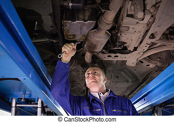 Concentrated mechanic repairing below of a car in a garage
