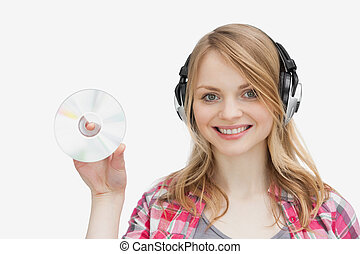 Woman holding a cd while wearing headphones