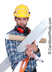 Construction worker overloaded with tools and building materials