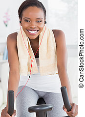 Black woman on an exercise bike listening music in a living...
