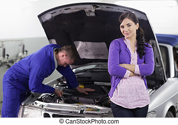 Woman leaning on a car next to a mechanic in a garage