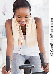 Black woman on a bike listening music while smiling