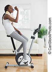 Side view of a black woman on an exercise bike in a living...