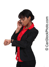 An African American businesswoman looking at her watch.