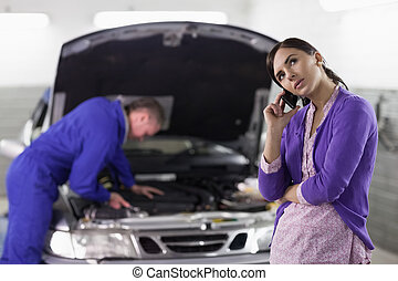 Client calling next to a mechanic in a garage