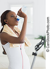 Black woman drinking water in a living room