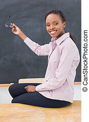 Teacher sitting on desk showing the blackboard in a...
