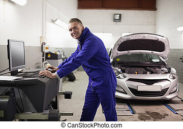 Smiling mechanic using a computer in a garage