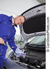Mechanic holding a dipstick in a garage