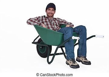 A man resting in a wheelbarrow.