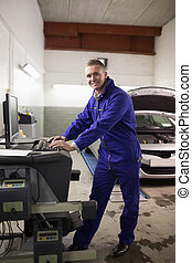Mechanic using a computer while smiling