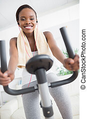 Front view of a black woman doing exercise bike in a living...