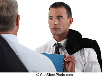 Young businessman listening to a senior colleague