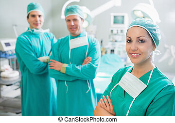 Surgical team with arms crossed in an operating theatre