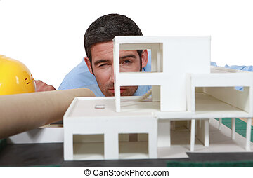Architect analyzing scale model of building