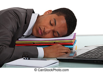 Worker sleeping on a stack of folders