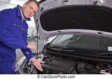 Mechanic showing an engine with his hand
