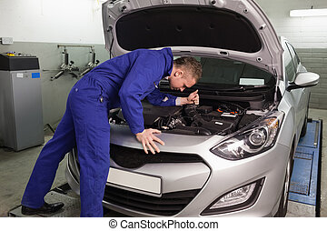 Mechanic looking at a car engine in a garage