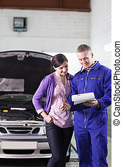 Mechanic showing a paper in a clipboard to a client in a...