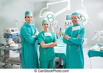 Surgeons with arms crossed smiling in an operating theatre