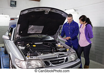 Mechanic showing a clipboard to a woman in a garage