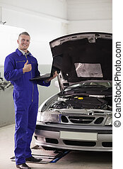 Smiling mechanic holding a computer with thumb up in a...